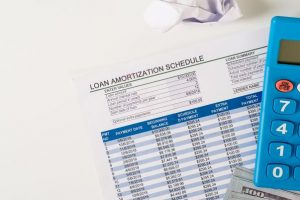 Personal financial planning concept. Loan schedule sheet,us banknote,calculator, flat lay on white background.